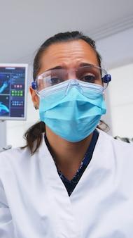 看護師が手術のためのツールを準備している間、歯痛のある人を口腔病学の椅子に座って検査するツールを保持する保護マスクの歯科医に対する患者の視点。