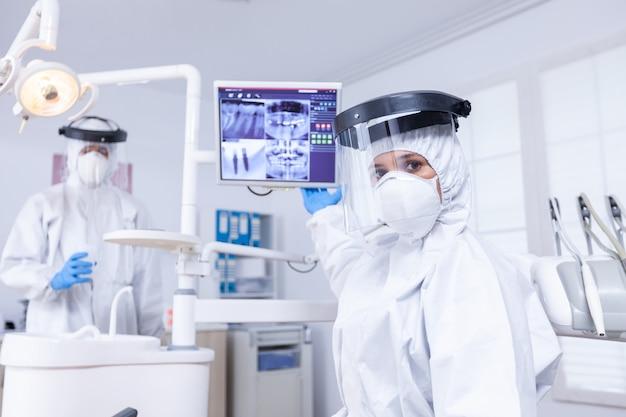 디지털 화면에서 치아 엑스레이에 대해 토론하는 치과 교정 의사의 환자. 구강 전문의는 방사선 촬영을 가리키는 코로나바이러스 감염에 대한 보호복을 입고 있습니다.