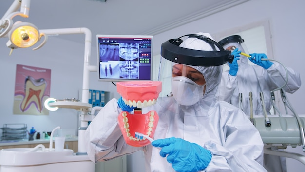 Patient pov of dentist medical team teaching child to clean teeth wearing precaution against covid in dental office using skeleton accessory. stomatolog wearing safety gear during heatlhcare check