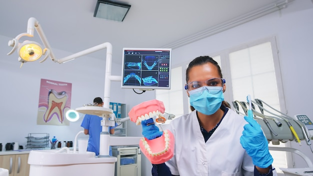 Patient pov of dentist teaching woman correct cleaning of teeth in dental office using skeleton accessory. stomatolog wearing protection mask asking for presentation teeth medical object