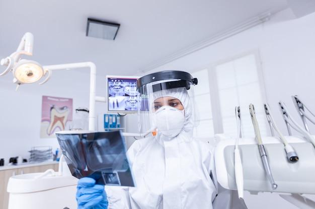 Covid-19 동안 보호 장비를 입은 방사선 사진을 들고 치과 의사를 보고 치과 사무실에서 환자 pov. 방사선 촬영을 보여주는 코로안바이러스에 대한 보호용 방호복을 입은 치과 전문의