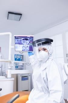 치과 의사가 엑스레이를 보여주는 치아 치료에 대해 이야기하는 의사를 듣고 있는 환자의 관점. radiogr을 가리키는 코로나바이러스 감염에 대한 보호복을 입은 구강 전문의