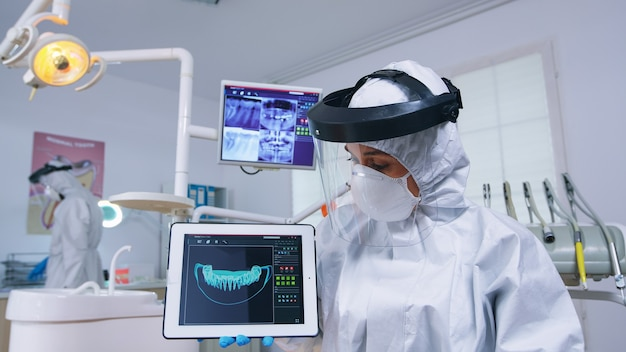歯の治療のための患者のハメ撮りリスニングの説明、つなぎ服の歯科医がタブレットでx線を示しています。レントゲン写真を指しているcovid19による感染に対する防護服を着ている口腔病学の専門家
