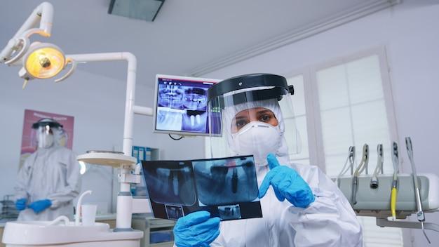 치과 사무실에서 엑스레이 이미지를 보여주는 ppe 정장에 치과 의사를보고 환자 pov. 새로운 정상으로 진료소에서 방사선 사진을 보여주는 코로안바이러스에 대한 보호용 방호복을 입은 구강 전문의