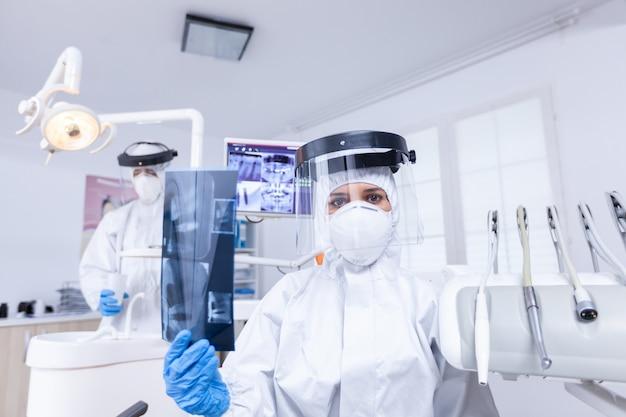 치과 사무실에서 엑스레이 이미지를 보여주는 치과 의사를 보고 환자 pov. 방사선 촬영을 보여주는 코로안바이러스에 대한 보호용 방호복을 입은 구강 전문의.