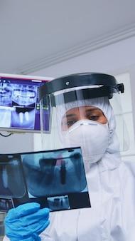Pov paziente che guarda il dentista in tuta dpi che mostra un'immagine a raggi x in studio dentistico. specialista in stomatologia che indossa una tuta ignifuga protettiva contro il coroanvirus che mostra radiografia in clinica con nuova normalità