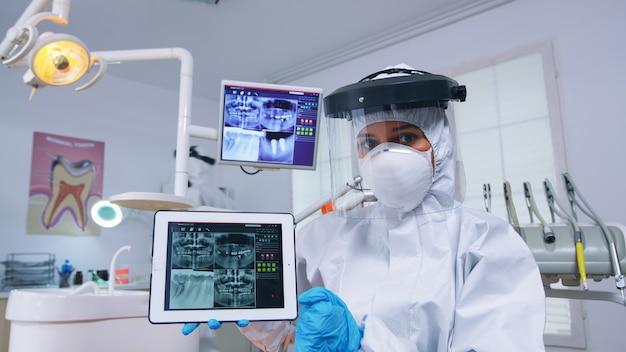 치과 방사선 촬영 및 태블릿을 사용한 치아 감염 진단을 설명하는 치과 팀의 환자 pov. x-레이를 보여주는 코로안바이러스에 대한 보호용 방호복을 입은 구강 전문의.