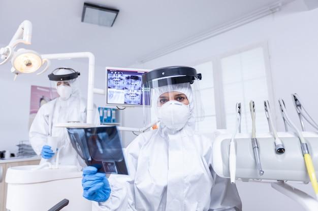 Covid gloabl 전염병 동안 환자 치아 엑스레이를 검사하는 치과 의사의 환자 pov. 방사선 촬영을 보여주는 코로안바이러스에 대한 보호용 방호복을 입은 구강 전문의.