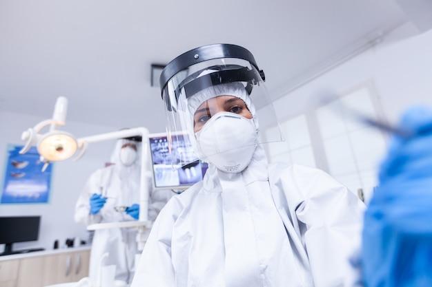 환자를 치료하는 covid 보호를 착용하고 치과 도구를 들고 치과 의사의 환자 pov. 환자의 건강을 확인하는 동안 코로나바이러스에 대한 안전 장비를 착용하는 stomatolog.