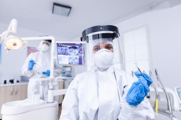 치과 사무실에서 치아 치료를 위한 도구를 들고 있는 치과 의사의 환자 pov. 환자의 건강을 확인하는 동안 코로나바이러스에 대한 안전 장비를 착용하는 stomatolog.