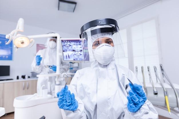 치과 사무실에서 그녀의 도구와 covid 보호 소송에서 치과 의사의 환자 pov. 환자의 건강을 확인하는 동안 코로나바이러스에 대한 안전 장비를 착용하는 stomatolog.