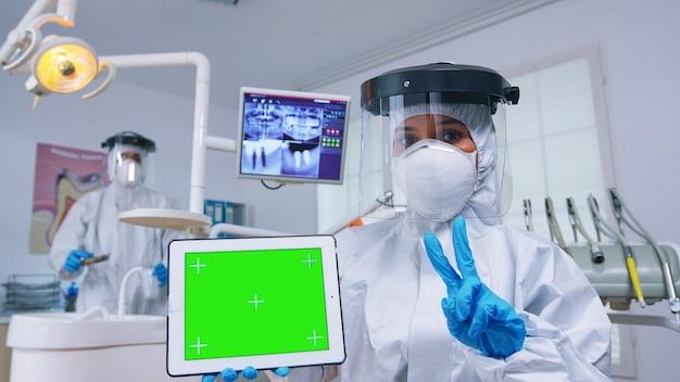歯科用x線撮影と緑色の画面のタブレットを使用した歯の感染症の診断を説明するppeスーツの歯科医の患者ハメ撮り。モックアップ、コピースペース、彩度表示を指す口腔病学の専門家