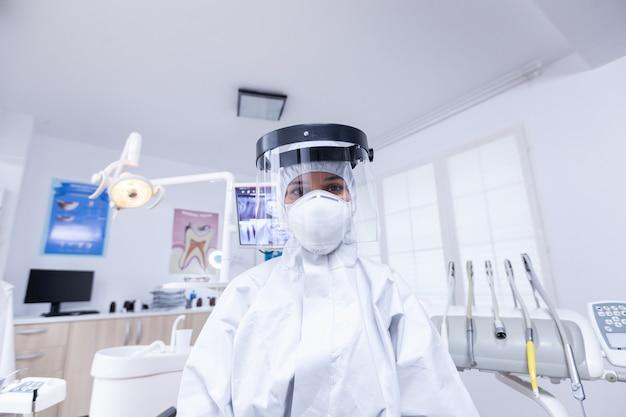 치과 사무실에서 covid 바이러스 감염에 대한 보호 장비에서 치과 의사의 환자 pov. 환자의 건강을 확인하는 동안 코로나바이러스에 대한 안전 장비를 착용하는 stomatolog.