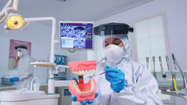 スケルトンアクセサリーを使用して歯科医院でcovidに対する予防措置を身に着けている歯をきれいにする正しい方法を示す歯科医の患者のハメ撮り。ヘルスケアチェック中に安全装備を着用した歯科医