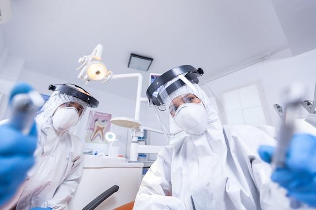교정 전문의와 보조원의 환자 pov는 작업복에서 구강 위생 절차를 수행합니다. 코로나바이러스 치료 환자에 대한 안전 장비를 착용하는 구강학 팀.