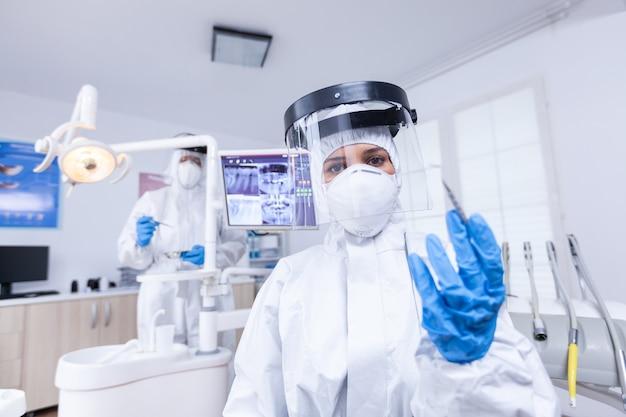 치과 사무실에서 치아를 치료하는 covid 보호에서 숙련된 치과 의사의 환자 pov. 환자의 건강을 확인하는 동안 코로나바이러스에 대한 안전 장비를 착용하는 stomatolog.