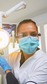 환자 pov는 영향을받는 질량을 치료하는 수술을 위해 치과 진료소를 방문합니다. 현대 교정 사무실에서 함께 일하는 의사와 간호사, 램프를 밝히고 보호 마스크를 쓴 사람을 검사합니다.