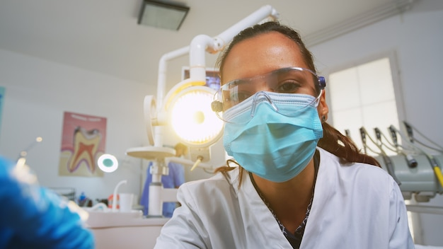 Patient pov visiting dental clinic for surgery treating affected mass. doctor and nurse working together in modern orthodontic office, lighting the lamp and examining person wearing protection mask.