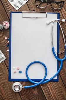 患者の医療カードのクローズアップ、聴診器、および医師の机の上の錠剤