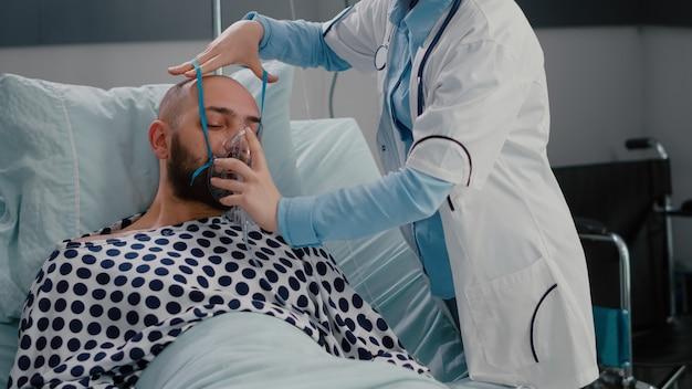 여자 의사가 호흡기 질환을 모니터링하는 산소 마스크를 두는 동안 침대에 앉아있는 환자