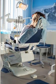 환자는 치과 의자에 앉아 치과 의사를 기다리고 있습니다. 구강 의학, 치과 치료, 예방, 건강 개념.