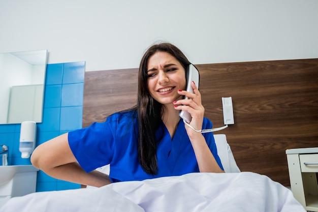 病院のベッドで電話で話している患者。若い白人女性。