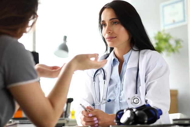 Patient talking with mature caucasian gp at her office