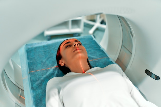 Patient undergoes an mri or ct scan under the supervision of a radiologist