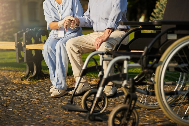자원 봉사자의 지원을받는 휠체어를 사용하는 환자