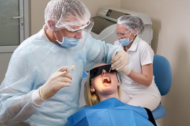 치과 사무실을 방문하는 환자. 성인 여자는 의자에 앉아. 치과 의사는 고무 보호 장갑을 착용합니다.