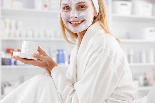 환자는 차를 마시면서 피부 관리 치료 결과를 기다립니다. 효과적인 절차. 얼굴에 마스크와 흰색 목욕 가운에 수석 여자.