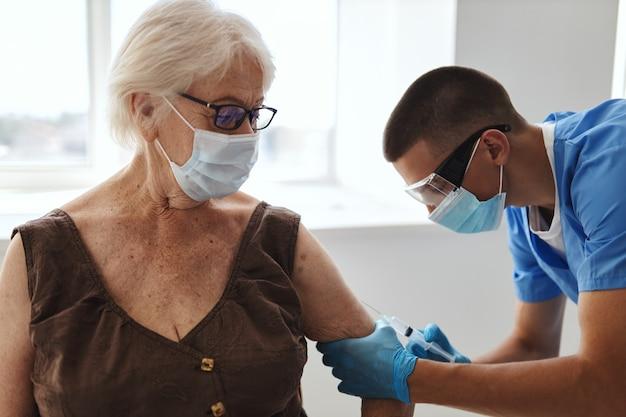 Пациент в медицинской маске в больнице на приеме у врачей, паспорт вакцины