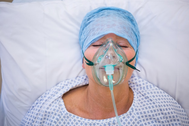 Patient wearing oxygen mask lying on hospital bed