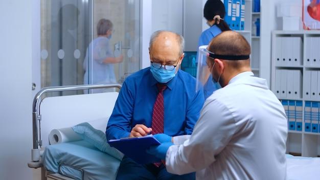Пациент носит защитную маску и подписывает выписку. консультация врача-медика covid-19 во время глобальной пандемии. частная современная поликлиника или больница, лечение медикаментами