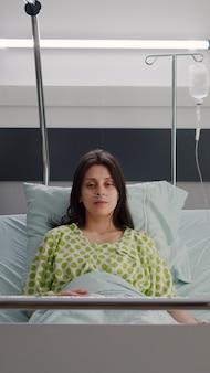 オンラインビデオ通話会議中にベッドに座ってカメラを見ている鼻酸素チューブを身に着けている患者