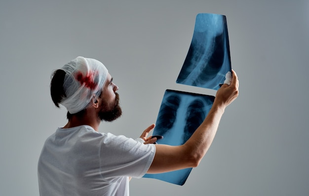 붕대 머리를 가진 환자는 회색 배경 의학에 엑스레이를 검사합니다