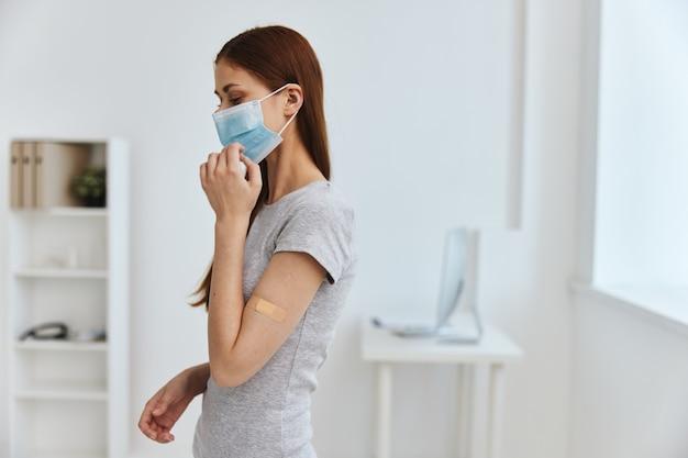 肩に粘着テープが貼られている患者と医療用マスク病院のcovidパスポートの健康