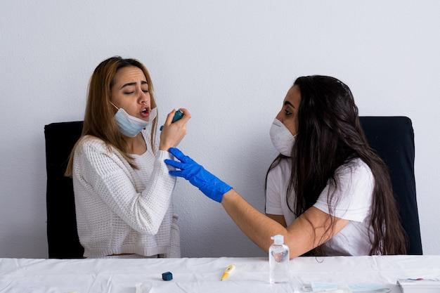 喘息と呼吸器系の問題を抱える患者が病院の看護師によって治療されています。コロナウイルスパンデミック。