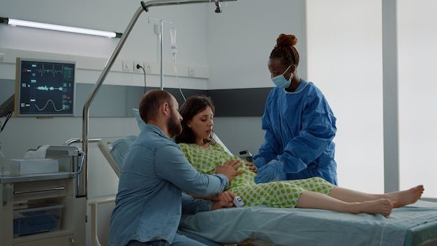 病棟のベッドに座っている赤ちゃんのバンプを持つ患者