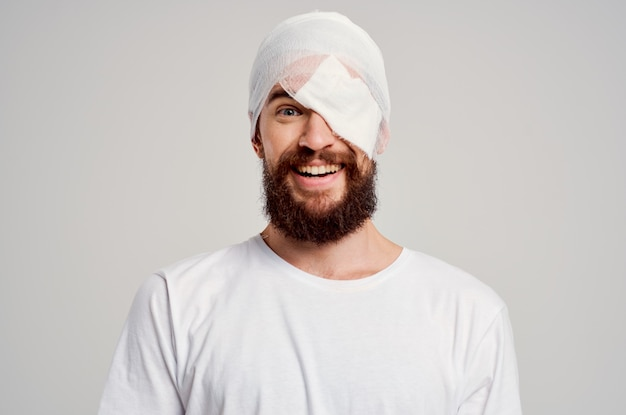 Patient with a bandaged head and an eye blood isolated background