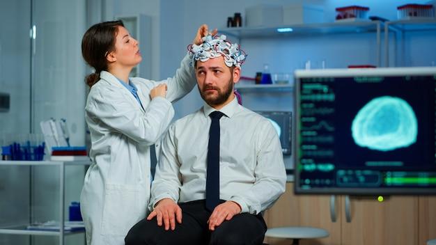 Paziente con scansione cerebrale che discute con il ricercatore medico neurologico durante la regolazione dell'auricolare per la scansione delle onde cerebrali esaminando la diagnosi della malattia, spiegando i risultati dell'eeg, lo stato di salute, le funzioni cerebrali
