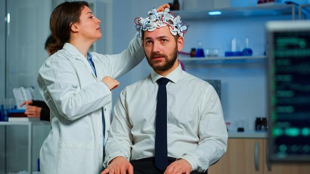 Пациент с гарнитурой для сканирования мозговых волн сидит в лаборатории исследования мозга, пока ученый-невролог настраивает высокотехнологичное устройство. мужчина посещает профессионального врача, лечящего дисфункции нервной системы
