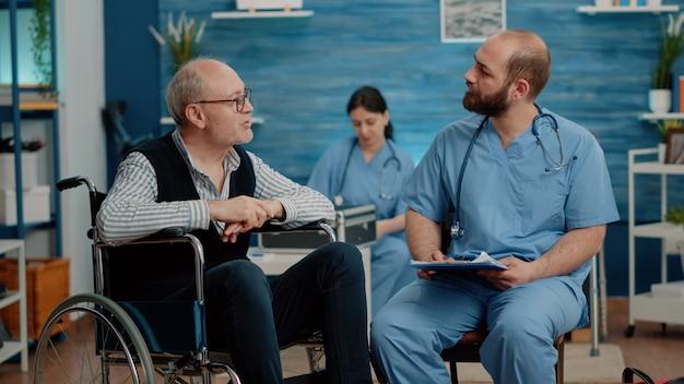 男性看護師と相談している障害のある患者 Premium写真