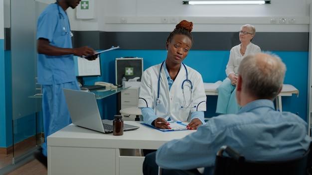 薬で健康診断のために机に座っている障害のある患者