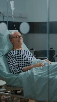 施設の病棟のベッドで眠っている病気の患者