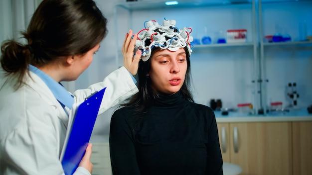 Пациент с гарнитурой eeg обсуждает с медицинским исследователем во время обследования, сидя на стуле в неврологической лаборатории