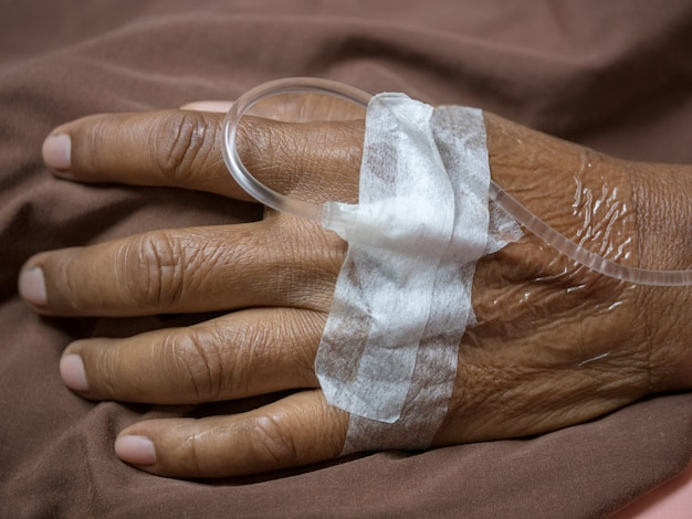 A patient with an intravenous line inserted into a vein in the hand.