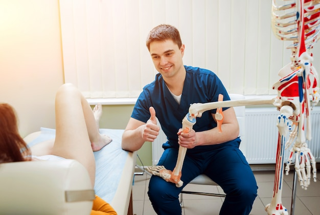 Patient with orthopedist doctor in his office.