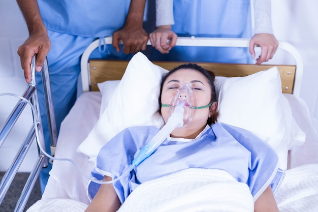 Patient with oxygen mask lying on bed and doctors standing near the bed