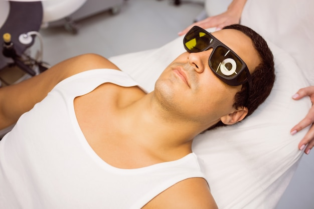 Patient with protective glasses lying for treatment
